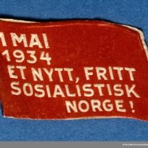 Arbeiderpartiets 1. mai-merke fra 1934 (OBS! er ikke i samlingen) men ligger i Arbeiderbevegelsen arkiv Bilde tilhører digitalt museum