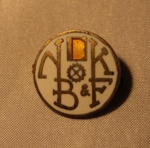 Norsk Bokbinder- og Kartonasjearbeiderforbund nål - stiftet i 1898 gikk inn i Norsk Grafisk Forbund i 1966 (gullskrift med hvit bakgrunn)