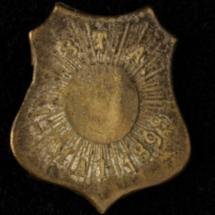 Arbeiderpartiets 1. mai-merke fra 1898 (OBS! er ikke i samlingen) men ligger i Arbeiderbevegelsen arkiv Bilde tilhører digitalt museum